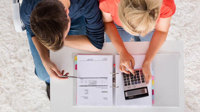 Couple Using Calculator For Calculating Invoice Tax Bills And Retirement Money On Desk At Home