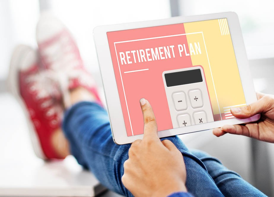 person sitting on at a desk with their feet up looking at a tablet that states retirement plan